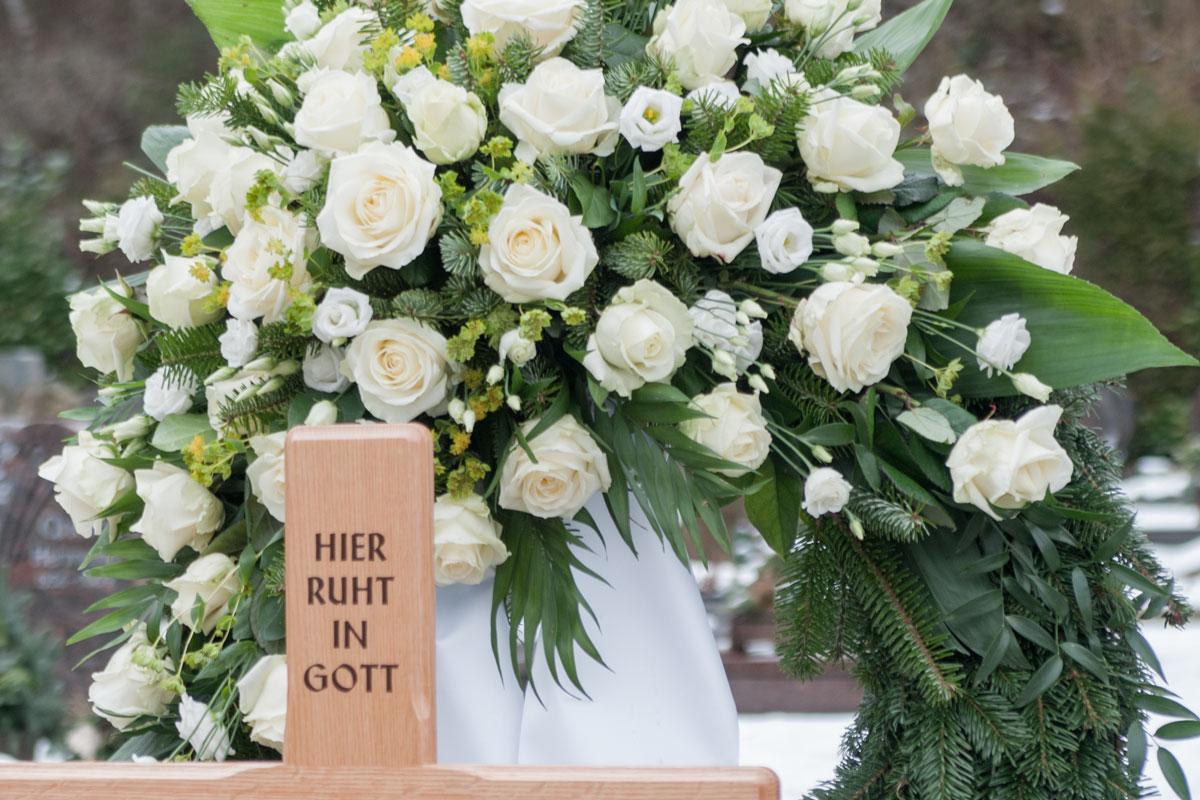 Ein klassischer Blumenschmuck: Trauerkranz mit Schleife. Doch Kränze zur Beerdigung sind keine Verpflichtung. Mehr dazu lesen Sie in unserem Beitrag.