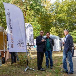 Banner im Vordergrund und Ronald de Schutter mit zwei weiteren Teilnehmern des Events Herbstwald erleben